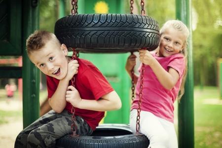 playground children: Ni�a y muchacho que tiene diversi�n en el patio