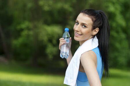 hacer footing: Mujer joven con la botella de agua Foto de archivo