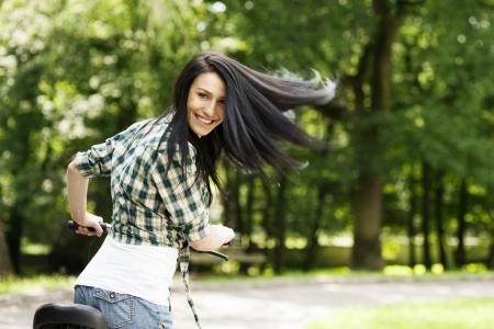 bicycle lane: Happy young woman with bike in the park