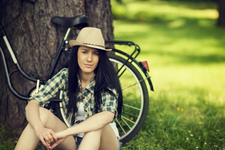 fedora hat: Beautiful young woman resting in park