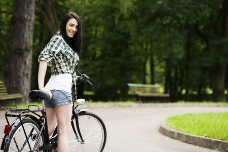 one lane: Beautiful young woman with bicycle in park