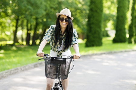 spring hat: Happy young woman cycling through the park Stock Photo