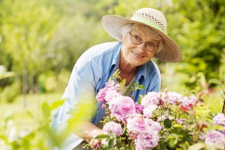 mujer con rosas: Superior de la mujer con flores en el jard�n Foto de archivo