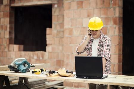 rolledup sleeves: Carpenter talking on mobile phone