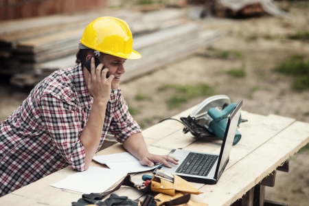 sawhorse: Carpenter talking on mobile phone
