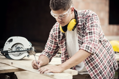 building worker: Carpenter measuring a wooden plank Stock Photo
