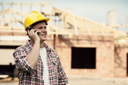 Construction worker with mobile phone photo