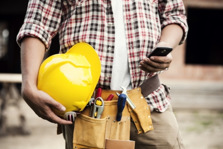 construction project: Close-up of construction worker texting on mobile phone
