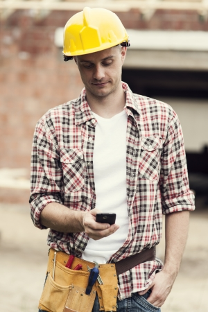 Construction worker texting on mobile phone photo