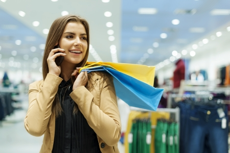 Young woman holding shopping bags and talking by phone photo