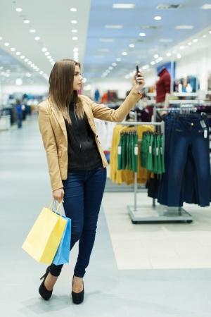 egy fiatal nő csak a: Fiatal nő bevásárló táskák és mobiltelefon
