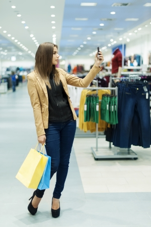 Young woman with shopping bags and mobile phone photo