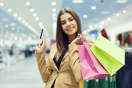 tarjeta de credito: Mujer joven con la tarjeta de cr�dito y la bolsa de la compra