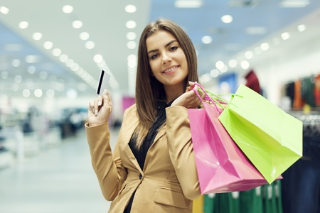 business card in hand: Young woman with credit card and shopping bag
