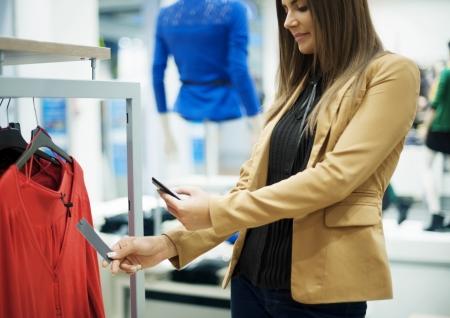 qr code: Smiling woman scanning QR code on smart phone