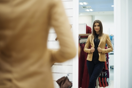 Beautiful young woman trying on jacket in front of mirror photo