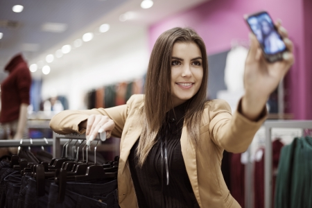 self portrait: Woman taking photo of herself in shopping mall