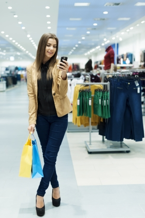 Happy young woman using smartphone in shopping mall photo