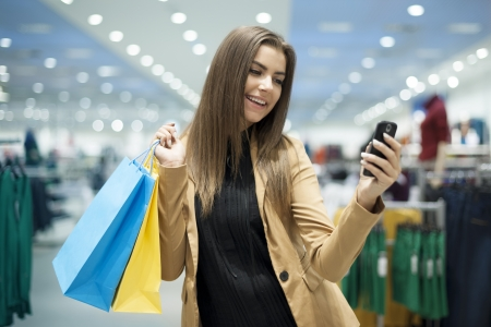 Cheerful female shopper texting on mobile phone photo