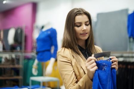 tienda de ropa: Hermosa mujer de cheques etiqueta en una boutique