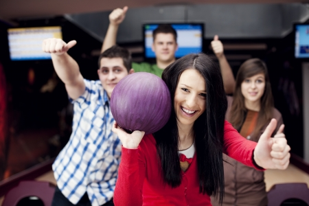 Friends bowling together photo