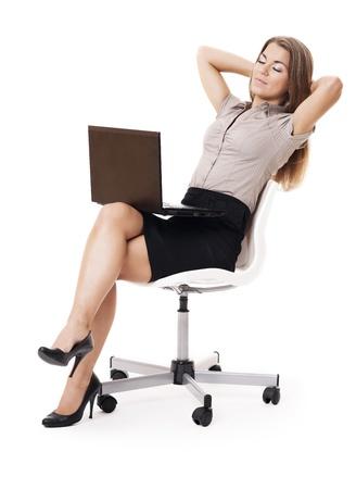 businesswoman suit: Empresaria con la computadora port�til que se relaja en silla de oficina