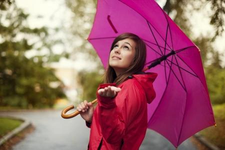 red umbrella: Beautiful woman with umbrella checking for rain Stock Photo