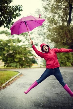 raincoat: Cheerful woman jumping with umbrella Stock Photo