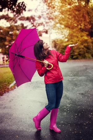 botas de lluvia: Mujer feliz con el paraguas de la comprobación de la lluvia en un parque Foto de archivo