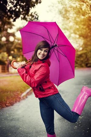 botas de lluvia: Mujer feliz con el paraguas rosado y botas de goma Foto de archivo