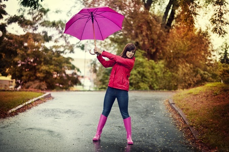 galoshes: Young woman holding pink umbrella in a park
