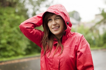 candid: Young woman in raincoat
