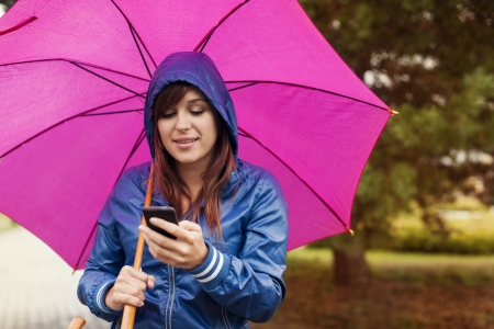 real people: Young woman texting on mobile phone in the rain