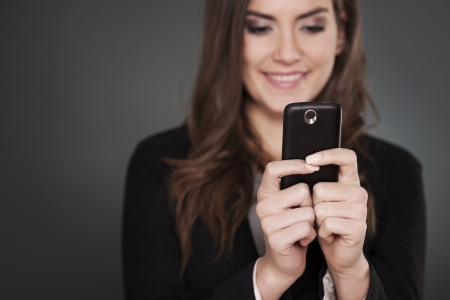 people on phone: Cheerful businesswoman texting on mobile phone