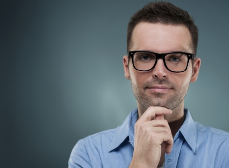 Attractive man in glasses and hand on chin photo