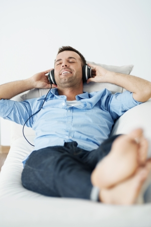 listening back: Cheerful man wearing headphones lying on the sofa Stock Photo