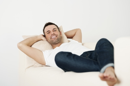 barefoot man: Happy male relaxing on couch at home