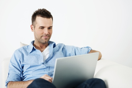 using the computer: Hombre atractivo usando la computadora portátil en el sofá