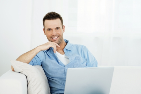 Portrait of handsome man with laptop on sofa photo