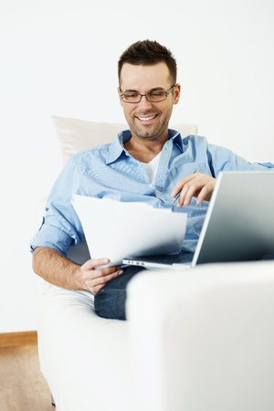busy beard: Handsome and smiling paying bills Stock Photo