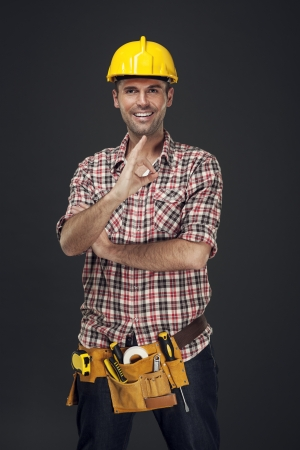 rolledup sleeves: Cheerful construction worker showing OK sign