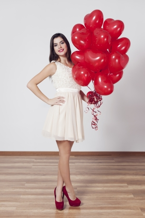 Woman holding many balloons in heart-shaped Stock Photo - 18190920