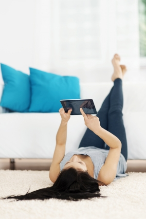 Young woman using tablet on the floor photo