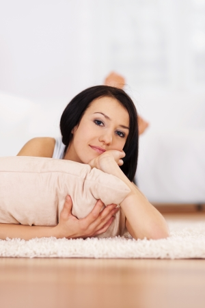Brunette woman lying down on the carpet photo
