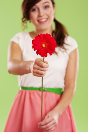 Young woman showing a red gerbera photo