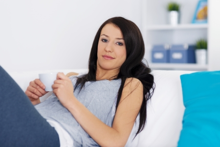 Woman relaxing on couch with cup of coffee Stock Photo - 18208285