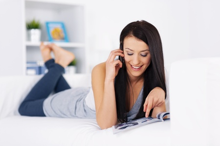 Young woman ordering something from a catalog Stock Photo - 18208206