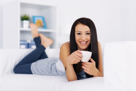 Woman relaxing on couch with cup of coffee Stock Photo - 18208256