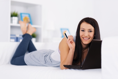 Young brunette lying on the couch with a credit card and laptop Stock Photo - 18208247