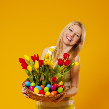 Happy woman holding basket with spring flower and easter eggs